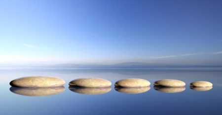 Zen stones row from large to small  in water with blue sky and peaceful landscape background.